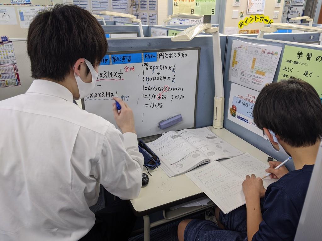授業の様子。ホワイトボードを活用してそれぞれの生徒の目標に合わせて指導します。生徒はノート記入を通して『自分だけの参考書』を作り、自宅での復習や学習習慣の形成に活かし、中学生の場合は学校へのノート提出の方法を学びます。