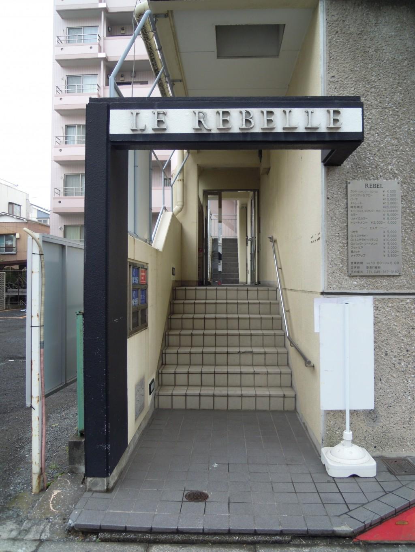 天王町スクールの入口です。美容室の隣の階段を上がって2階に受付がございます。